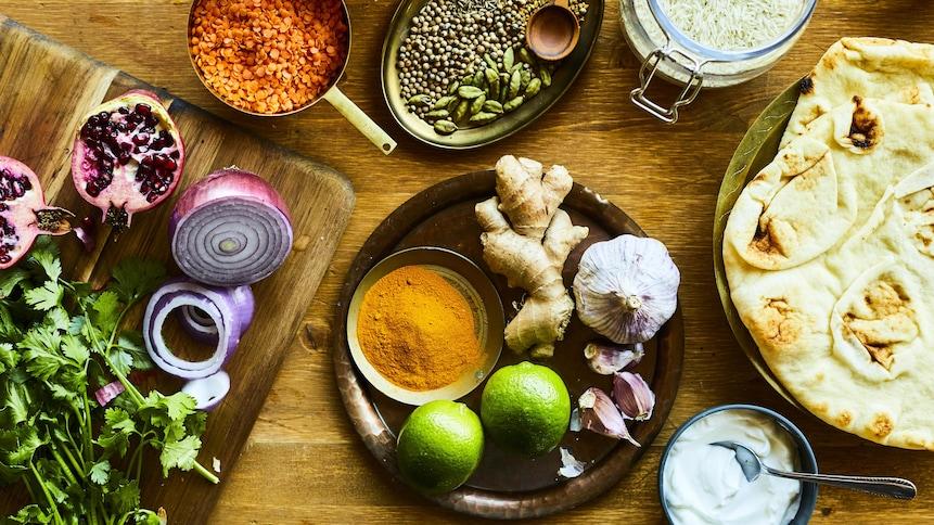 Sur une table en bois, des ingrédients ont été rassemblés. On y retrouve des épices, du gingembre frais, deux citrons verts, un duo de gousses d'ail, de la coriandre et un oignon rouge tranché en deux.
