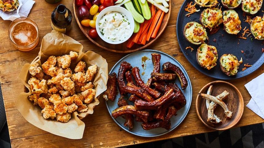 Une table basse sur laquelle sont déposées des assiettes de côtes de levées, de bouchées de chou-fleur Buffalo, de pelures de pommes de terre gratinées et de crudités avec une trempette.