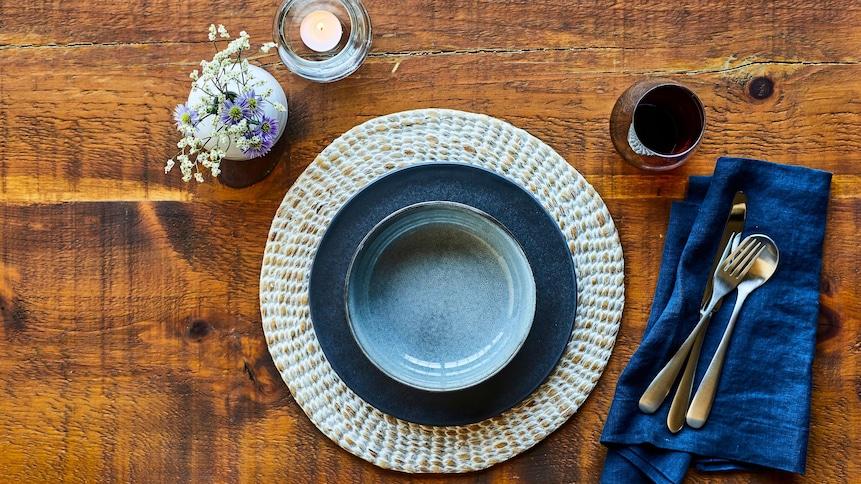 Bol et assiette posés sur un napperon rond, accompagnés d'un verre de vin, d'une bougie et d'un petit bouquet de fleurs.