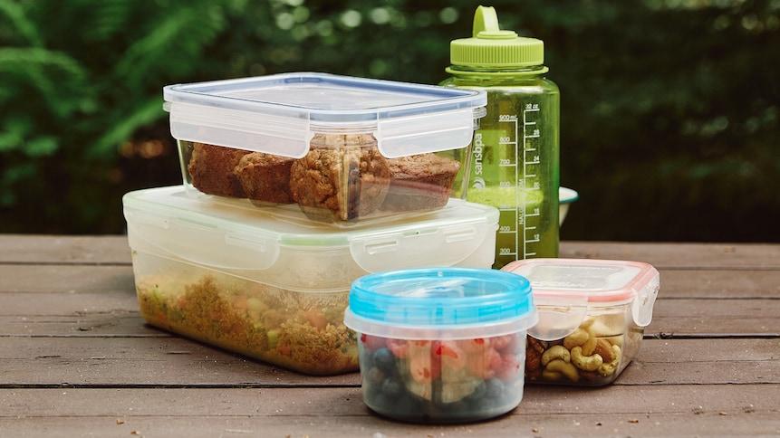 Sur une table à pique-nique, est déposé plusieurs contenants en plastique qui eux, contiennent une salade de couscous, des petits fruits et des noix. Il y a aussi une bouteille d'eau sur la table.
