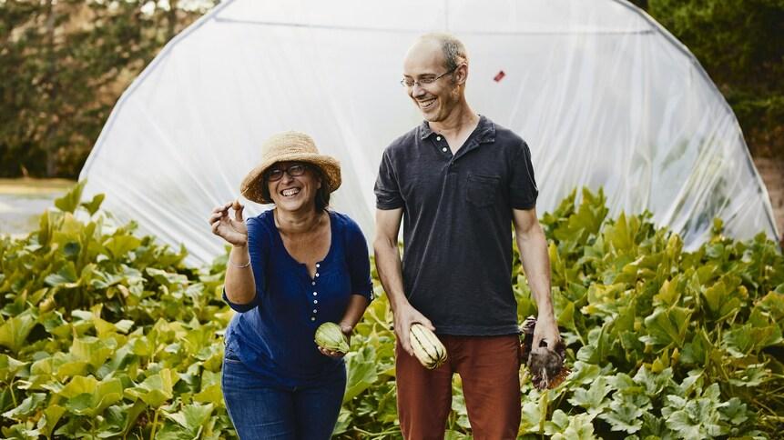 Il y a deux personnes devant une serre tenant à la main des légumes biologiques.