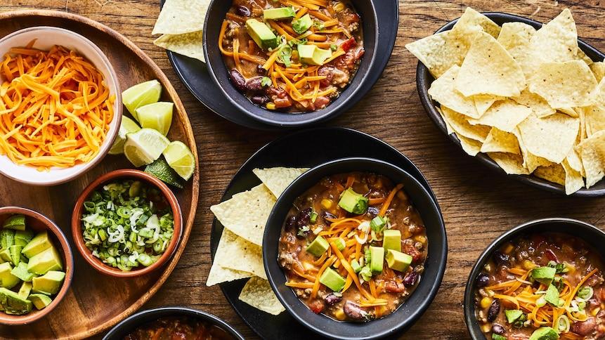 Plusieurs bols de soupe tacos avec ses options de garnitures : fromage, avocat, lime, chips.