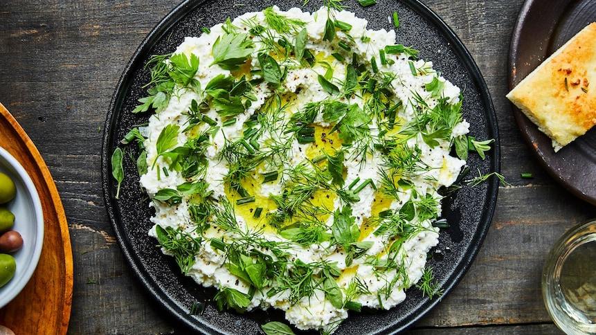 Du fromage ricotta avec des fines herbes dans une grande assiette noire.