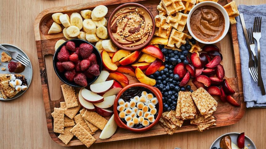 Sur une table en bois, est déposé un cabaret en bois comprenant plusieurs sortes de fruits tranchés avec des biscuits, des morceaux de gaufres et des trempettes au chocolat.