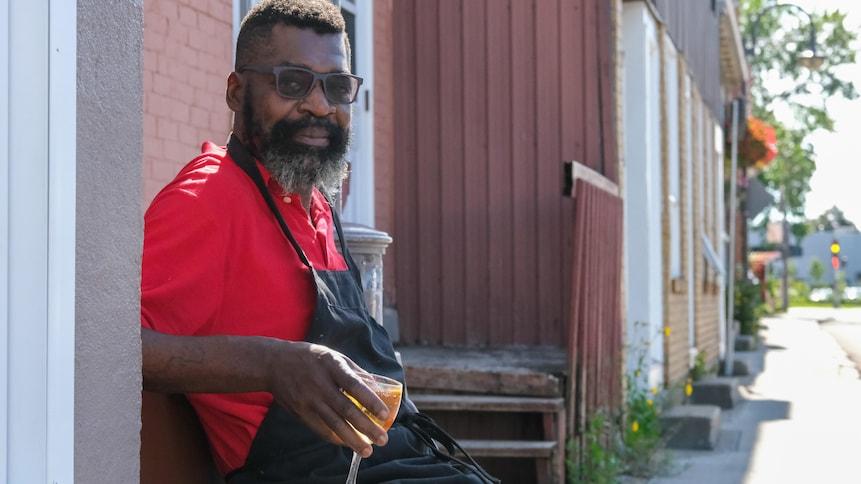 Un homme assis sur un banc regarde la caméra.