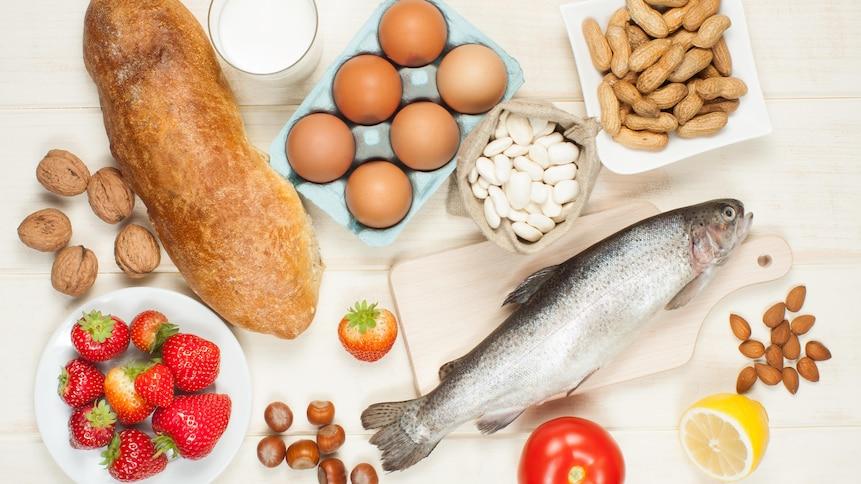 Une table sur laquelle se trouvent différents aliments allergènes : du pain, des oeufs, du lait, du poisson, des noix, des arachides, etc.
