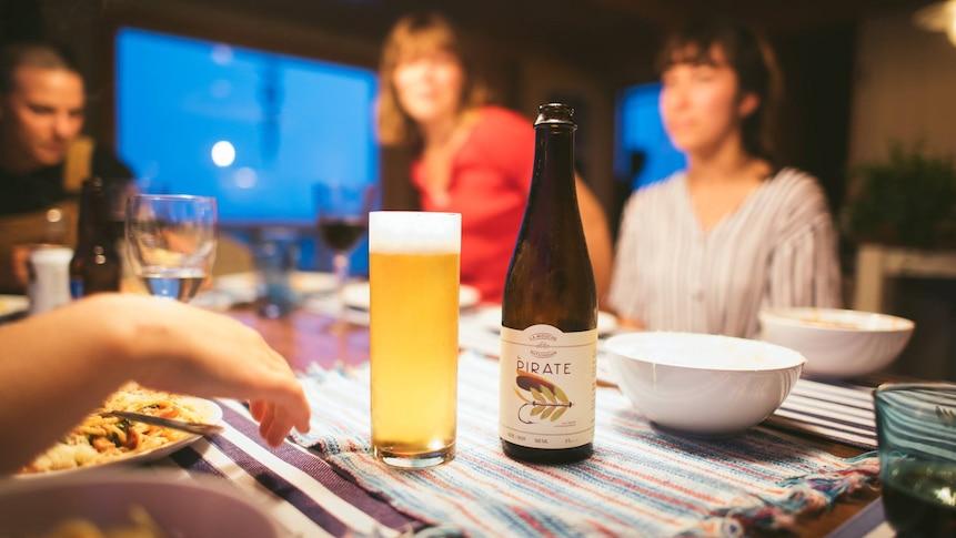Une bière posée sur une table entourée de convives.