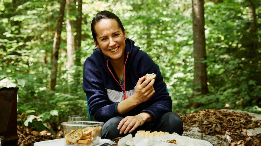 Geneviève O'Gleman en camping qui déguste des croutons de pain avec un fromage cuisiné sur un feu de camp.