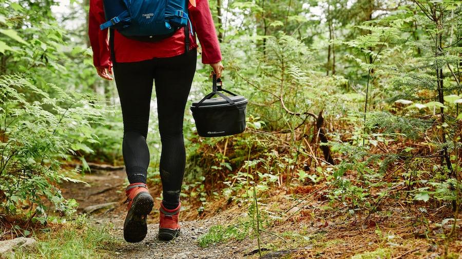 Une femme de dos en forêt qui transporte du matériel de camping.