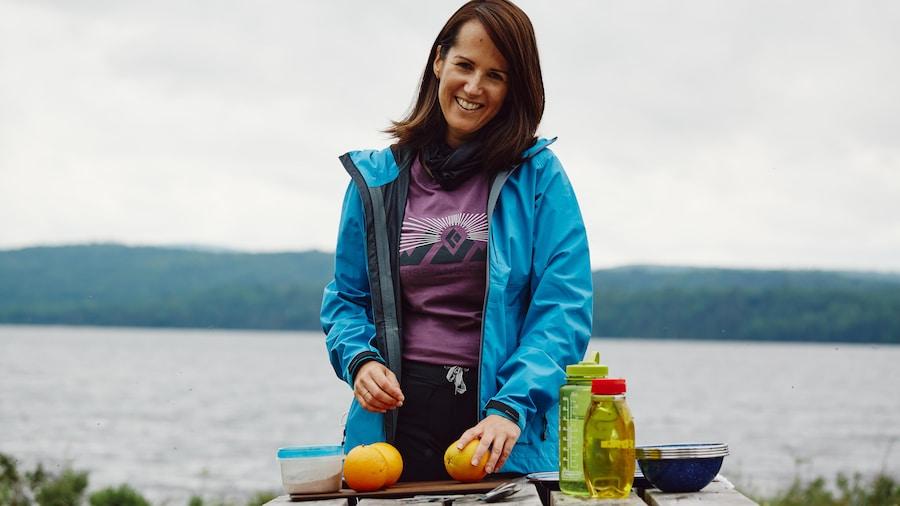 Geneviève O'Gleman devant une table à pique-nique qui se prépare à cuisiner avec des oranges.