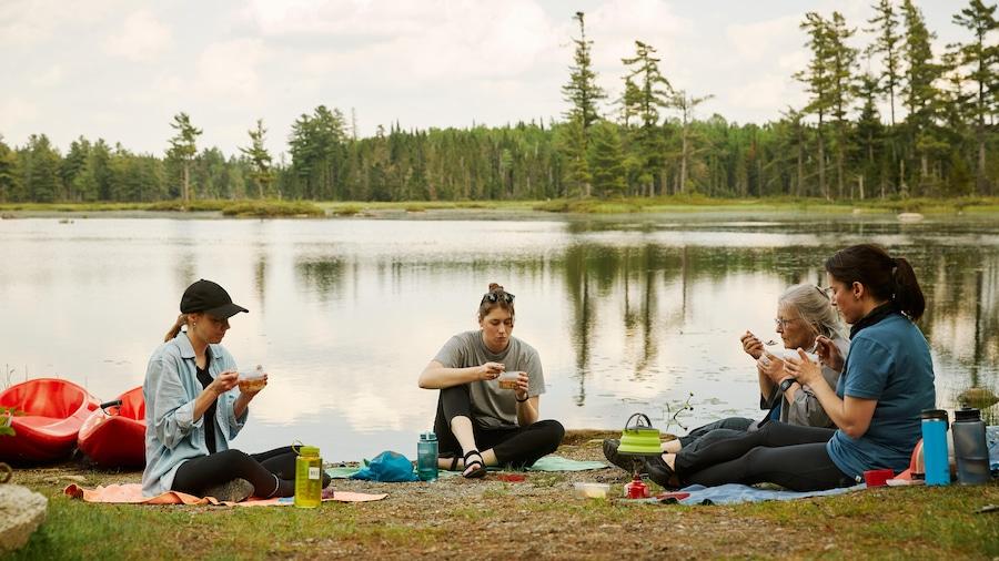 Quatre femmes assises au bord d'un lag qui dégustent une soupe.