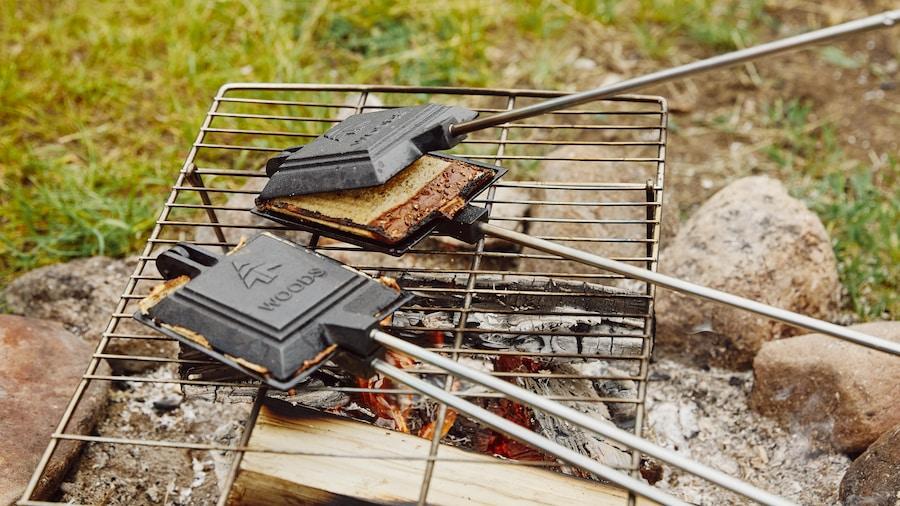Des sandwichs grillés cuisinés sur un feu de camp.