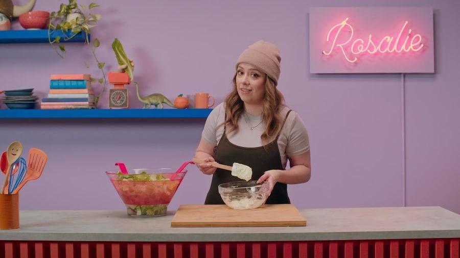 Rosalie tient dans sa main une spatule à pâtisserie au-dessus d'un pot en vitre.