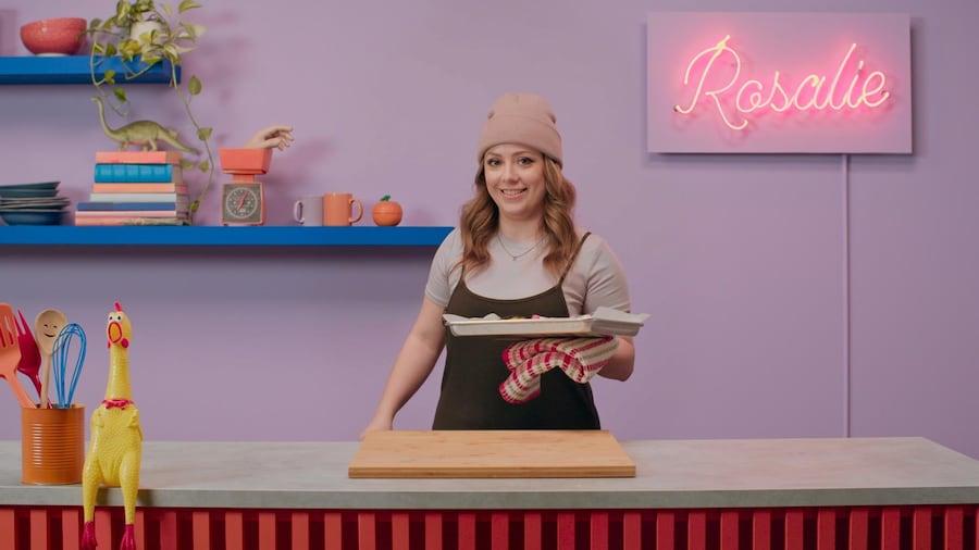 Rosalie tient dans sa main une plaque de cuisson contenant les poitrines de poulet.