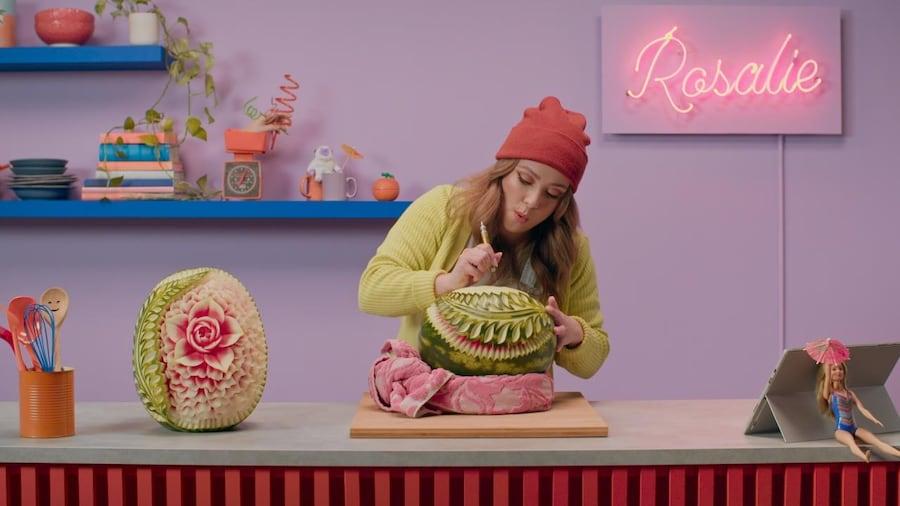 À l'aide d'un outil tranchant et fin, Rosalie taille le melon d'eau.