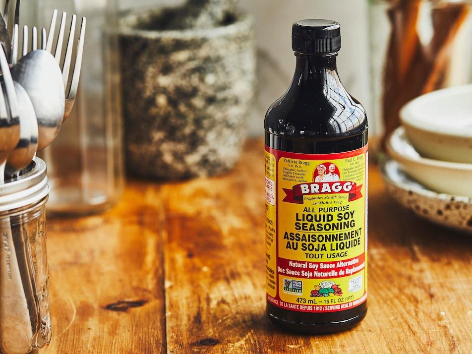 Une bouteille d'assaisonnement au soja liquide sur un comptoir de cuisine, entourée d'ustensiles et de vaisselle.