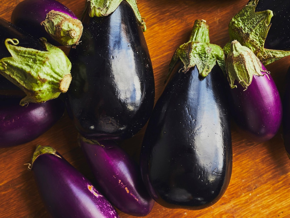 Des aubergines de différentes tailles et de couleurs variées sur un comptoir en bois.