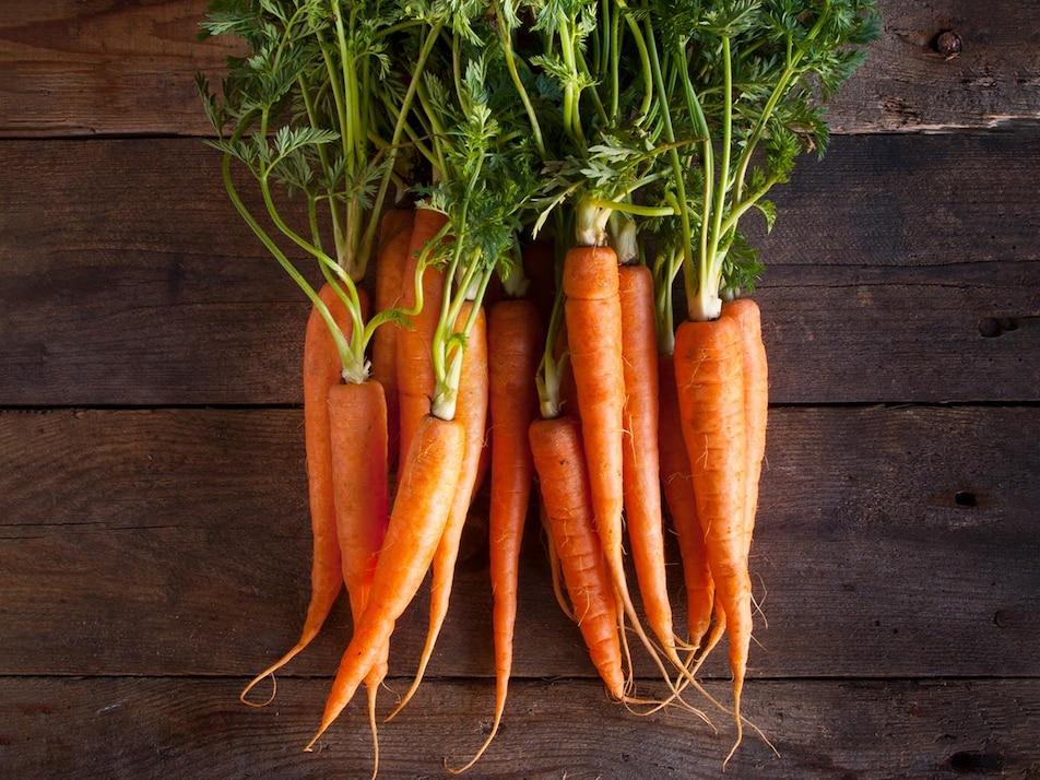 Plusieurs carottes entières avec les feuilles.