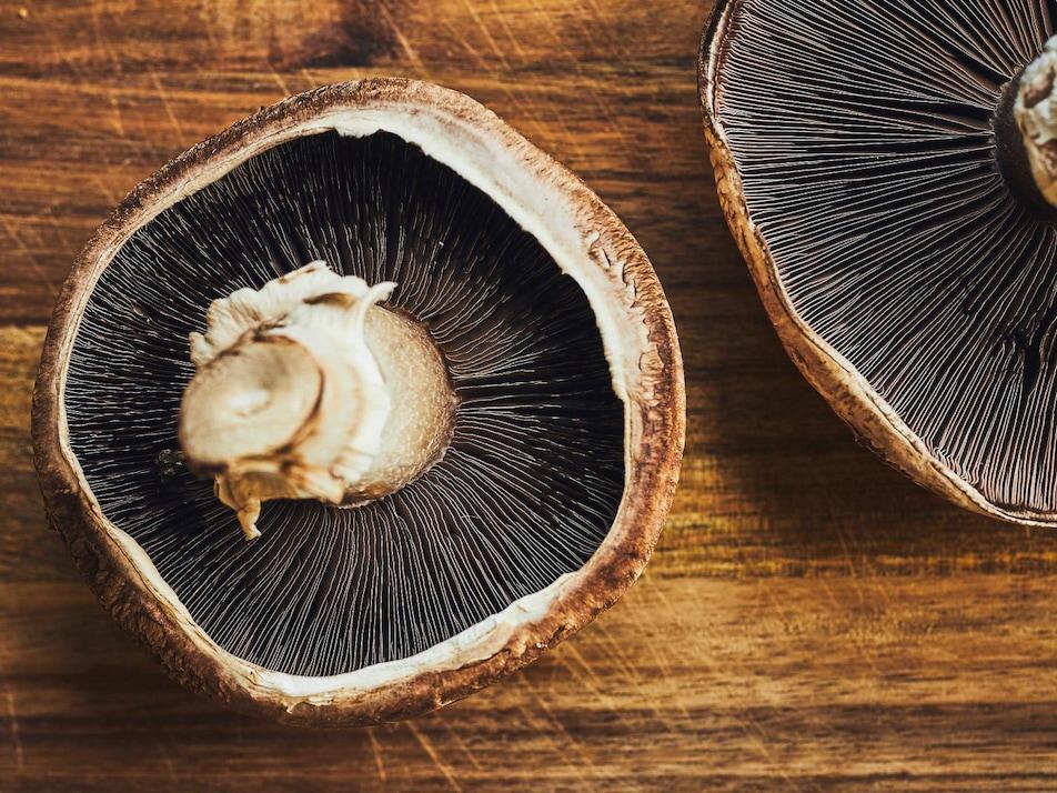 Deux champignons portobellos sur un comptoir en bois.