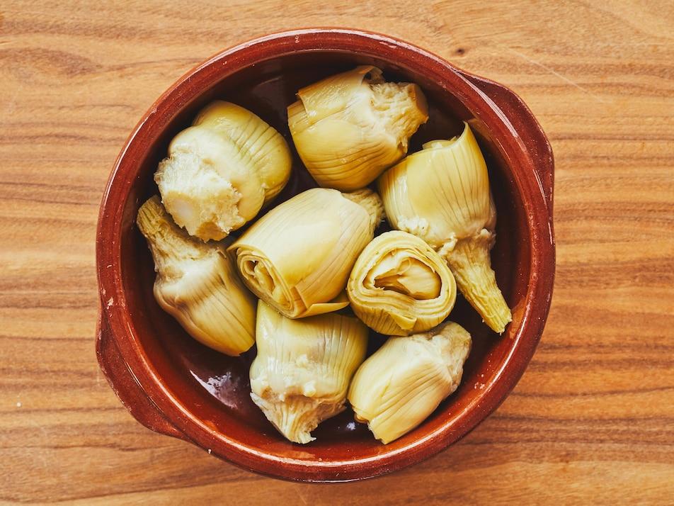 Des coeurs d'artichauts dans un bol sur un comptoir de bois.