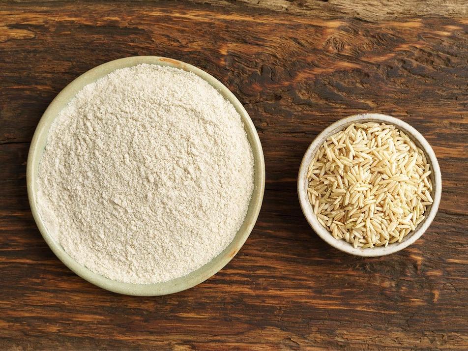 Un bol rempli de farine de riz ainsi qu'un autre bol rempli de grains de riz.