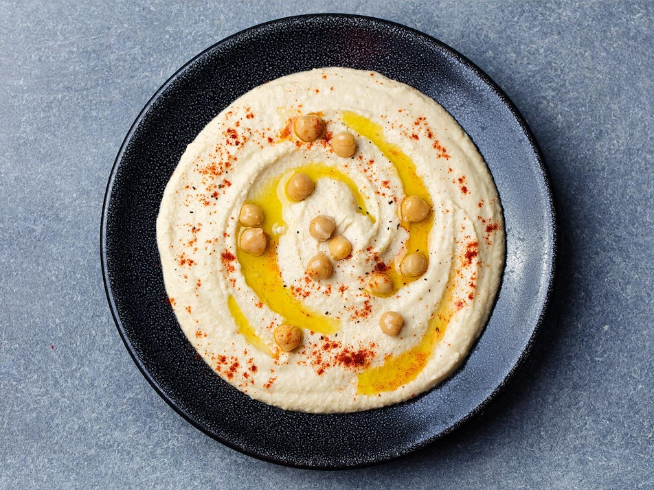 Un bol avec du houmous garni de pois chiches, d'épices et d'huile d'olive.