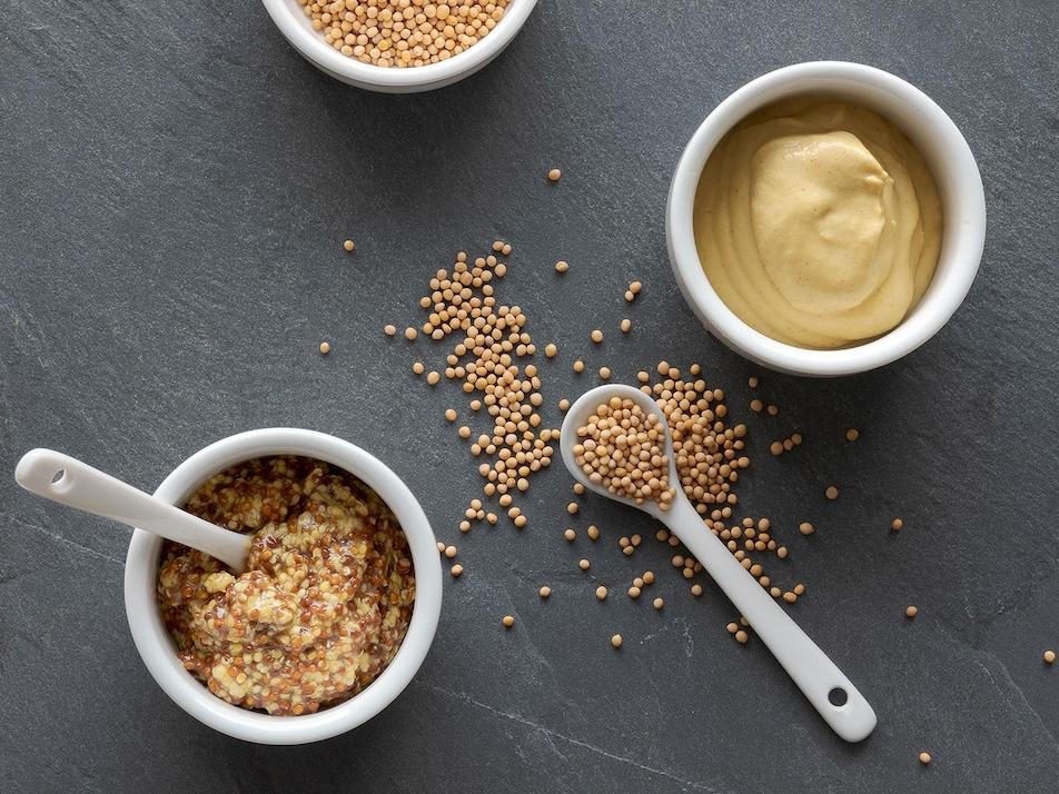 De la moutarde en grains dans un bol et dans une cuillère.