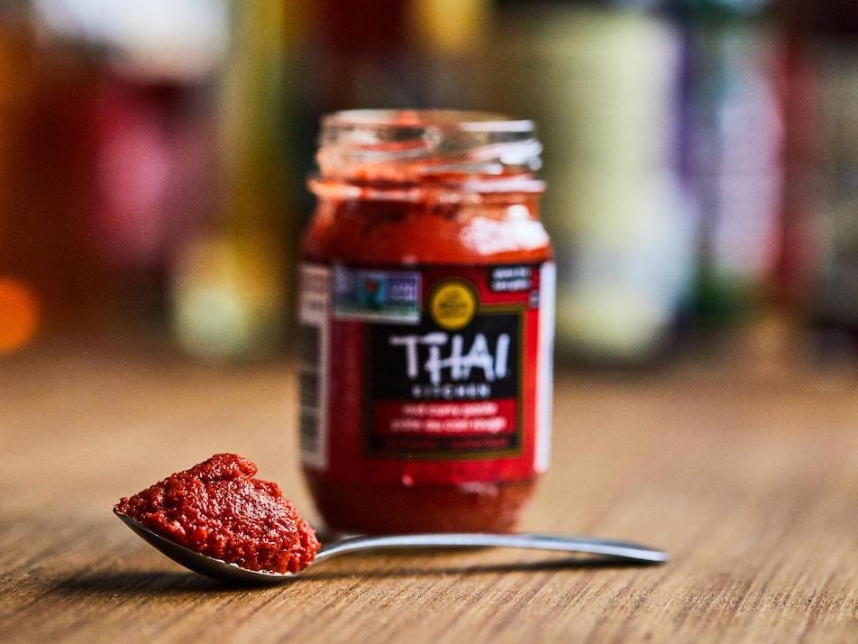 Une cuillerée de pâte de cari rouge thaï devant le contenant d'origine.