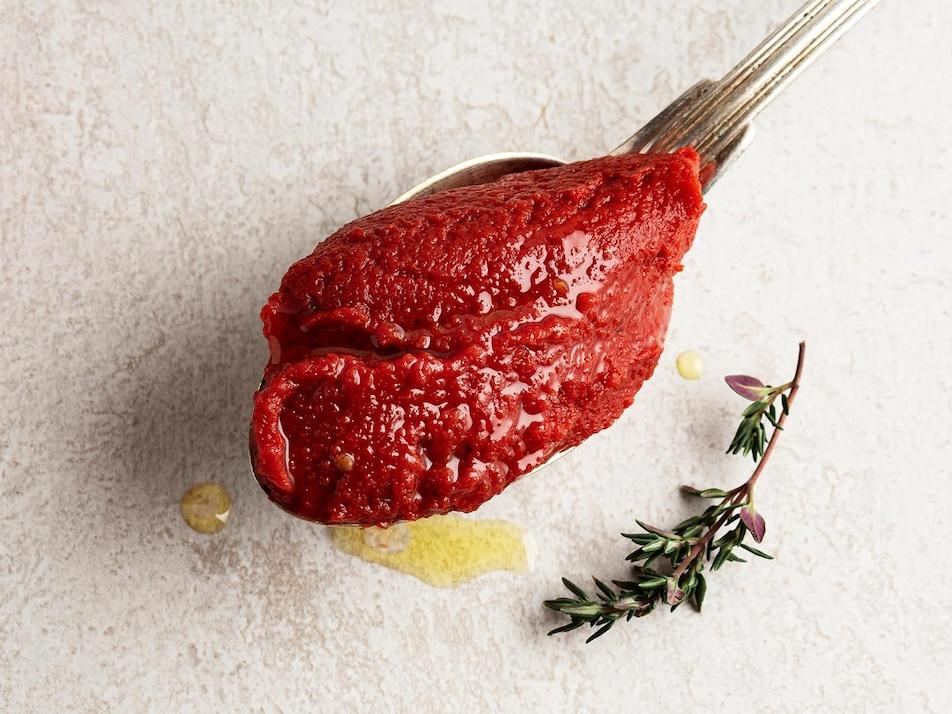 De la pâte de tomates dans une cuillère.