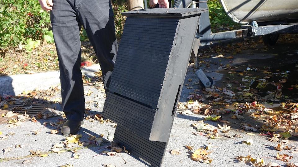 Une boîte noire présente des rayures creusées à même le bois.
