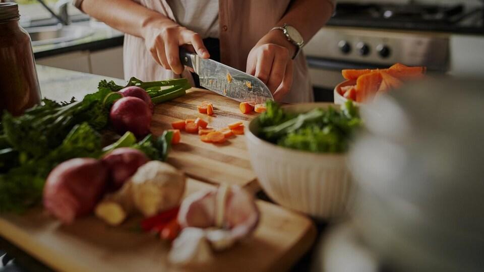 Des carottes se font découper sur un comptoir, sur une planche à découper.