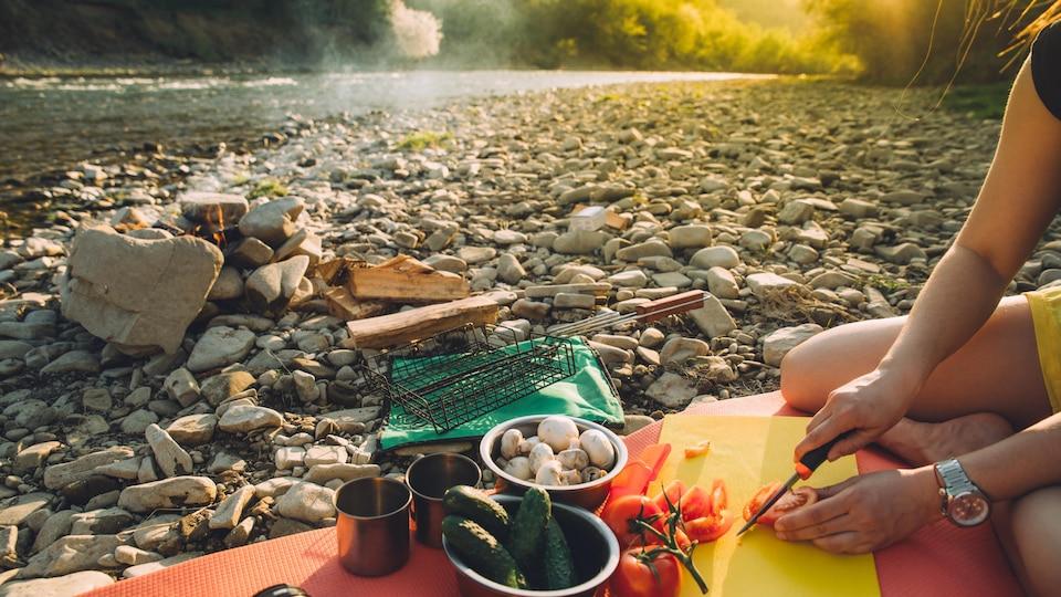 Une personne coupe une tomate, assise sur une plage de galets. À côté de cette personne, des bols remplis de concombre et de champignons prêts à être cuisinés sur un feu de camp.
