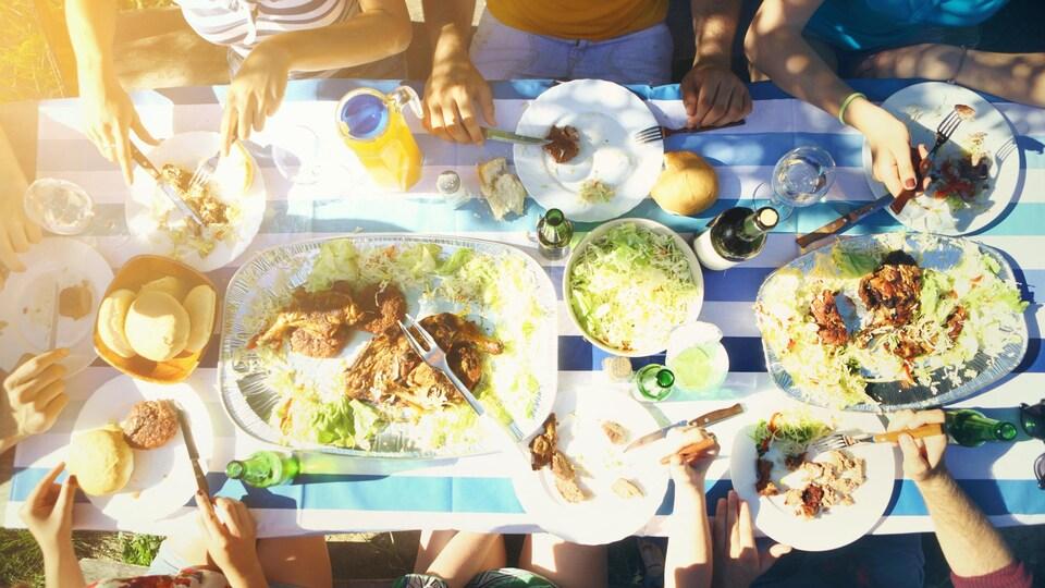 Un goupe de personnes est en train de manger à l'extérieur.