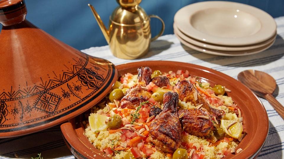Un plat de tajine avec du couscous, des olives vertes, quelques légumes et de la viande.