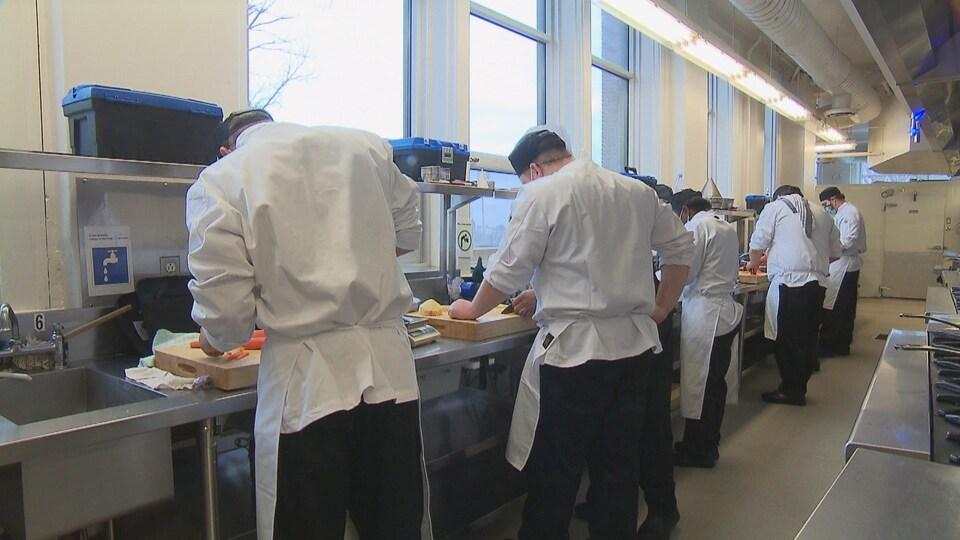Des cuisiniers de dos devant un plan de travail.