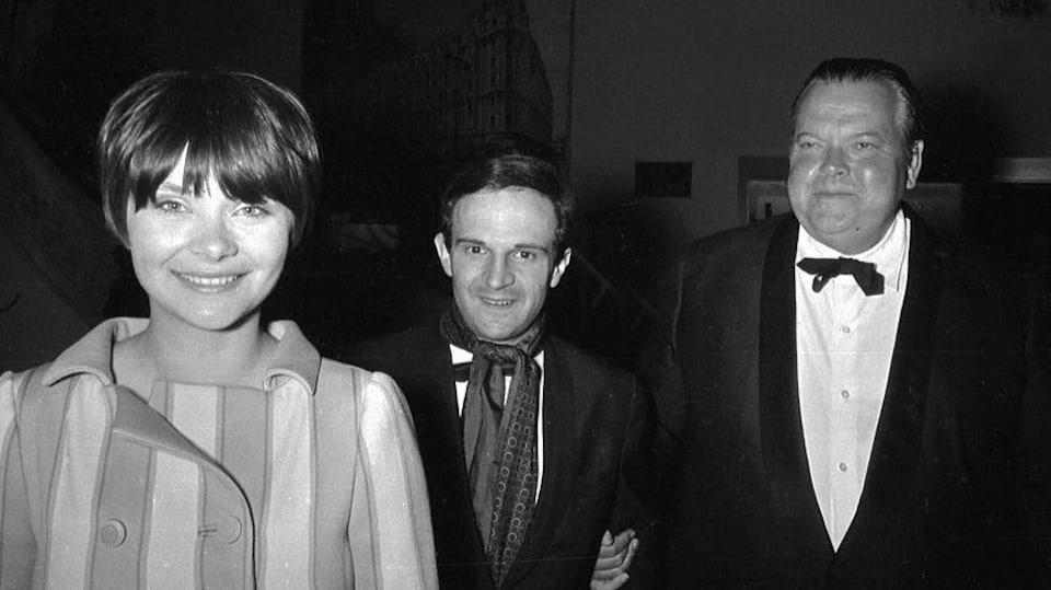 Les trois artistes, vêtus de leurs habits de gala, sourient sous le flash du photographe.