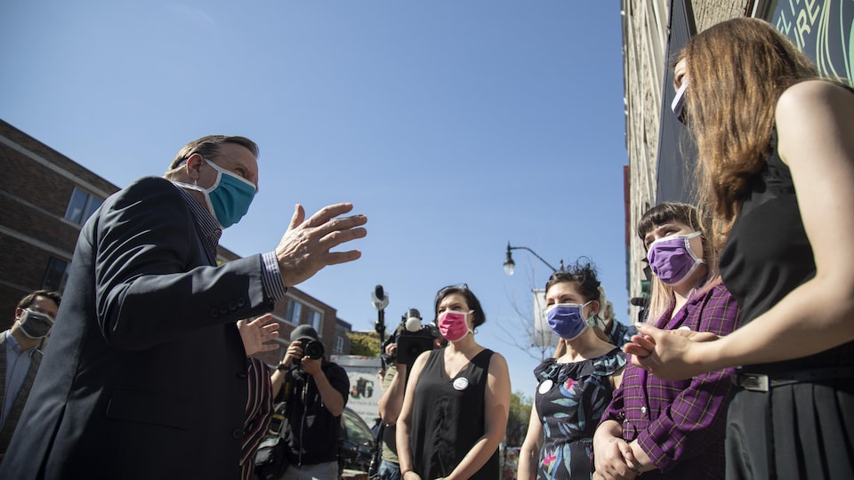François Legault discute avec un groupe de femmes, tout le monde est masqué.