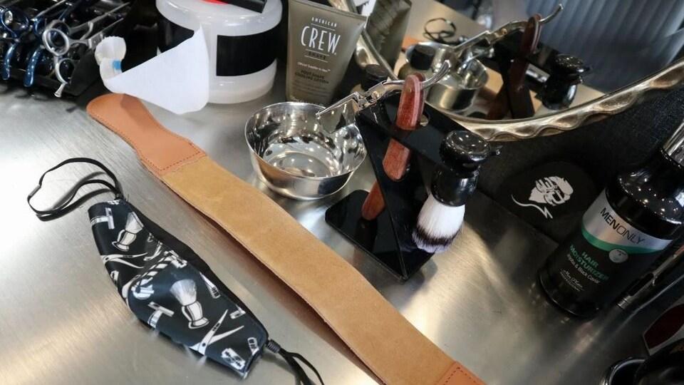 Comptoir sur lequel reposent des produits de rasage et un masque réutilisable.