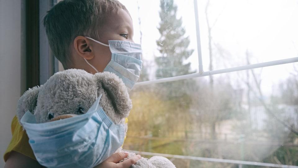 Un enfant avec un masque regarde par la fenêtre avec son toutou.