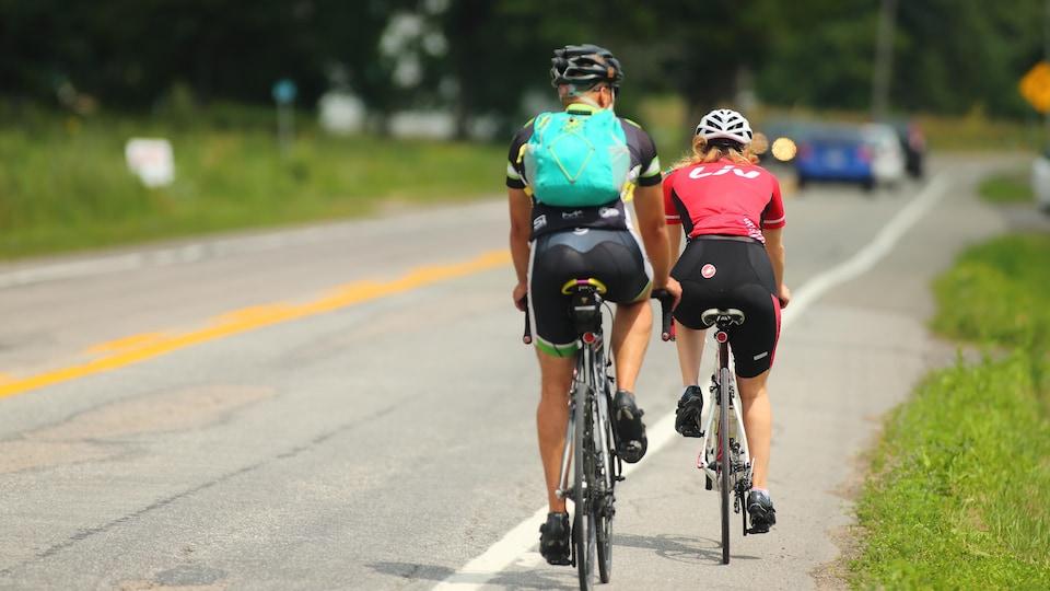 Deux cyclistes sur une route de campagne.