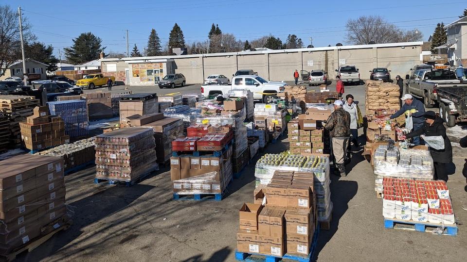 Quatre personnes remplient leurs sacs d'épicerie à partir de nombreuses palettes de boîtes de nourritures installées dans un stationnement.