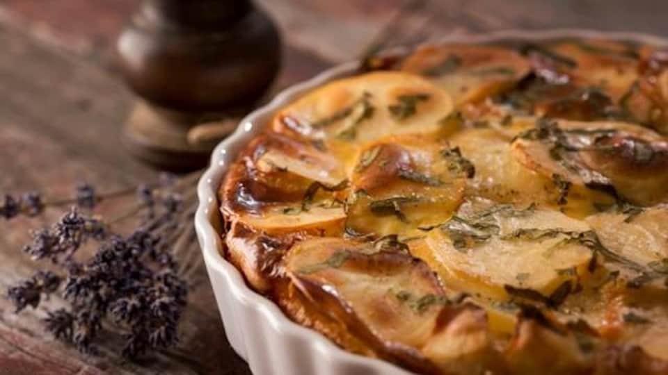 Un plat de pommes de terre dans un plat à tarte sur une table en bois.