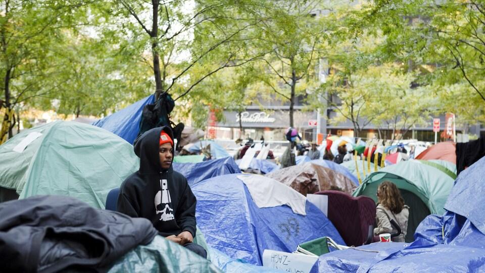 Un homme assied et entouré de tentes dans le parc Zuccotti à New York, lors d'Occupy Wall Street