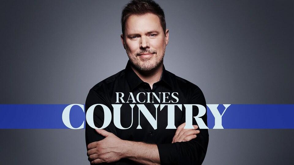 Jean François Breau regardant la caméra et souriant, avec les bras croisés. Devant lui, on peut lire le nom de l'émission Racines country.