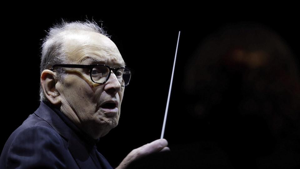 Ennio Morricone agite une baguette de maestro.