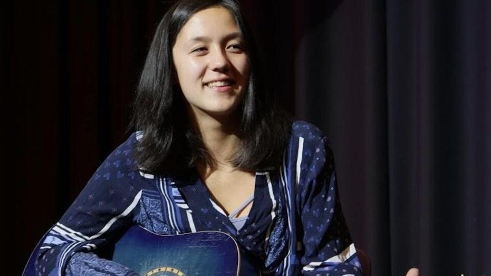 Serena Wu, sur une scène, jouant de la guitare.