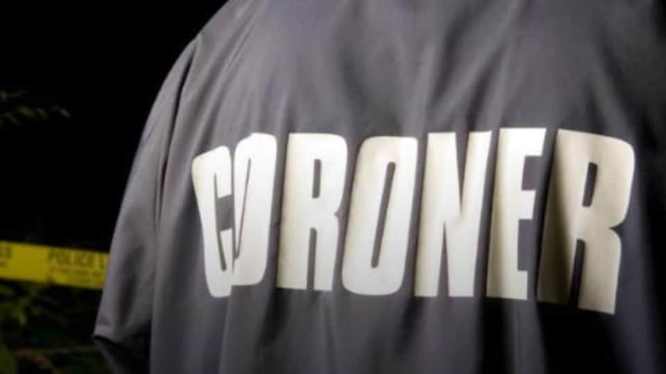 Une personne de dos près d'un cordon de sécurité avec un manteau sur lequel est écrit : coroner.