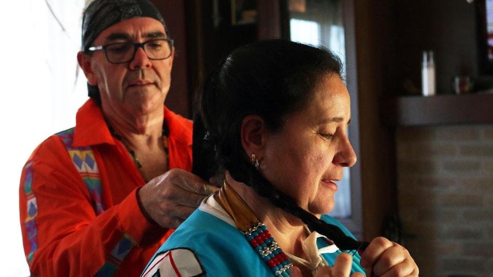 Un homme en arrière-plan tresse les longs cheveux noirs d'une femme au premier plan. Elle est vêtue d'un habit traditionnel.