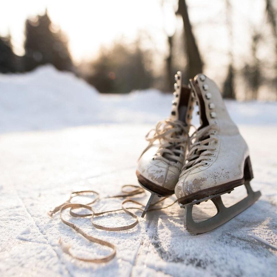 Photo d'une vielle paire de patins blanc sur une patinoire extérieure.