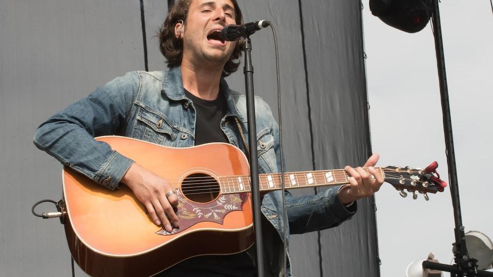 Chanteur avec sa guitare bouche ouverte devant un micro.